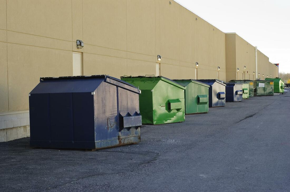 lines of medium sized commercial dumpsters for rent