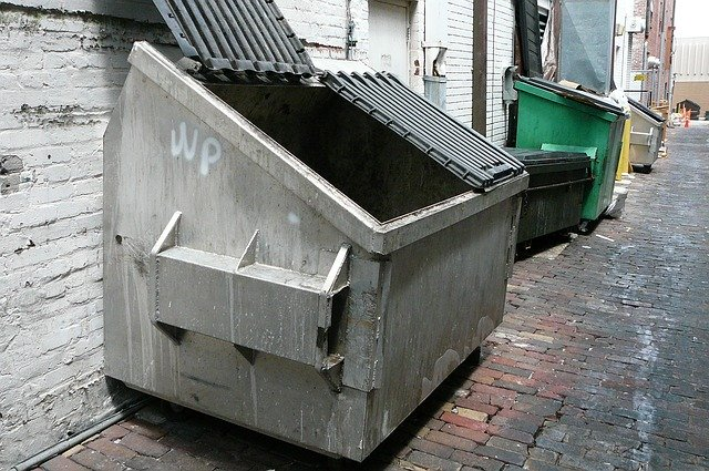 Several dumpsters for rent in an alley